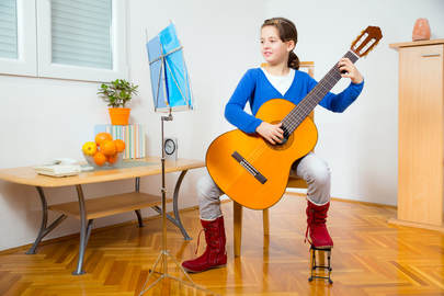 Young girl practicing classical guitar and reading music at her home in Providence, RI.