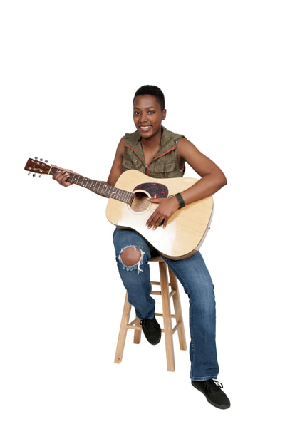 woman sitting on stool holding an acoustic guitar.