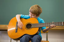 Boy posing during a guitar lesson.
