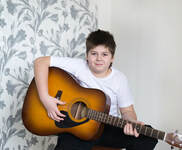 Teenage boy guitar student holding his acoustic guitar and posing for the camera.