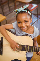 Young female guitar student holding acoustic guitar and smiling for her picture during her guitar lesson.