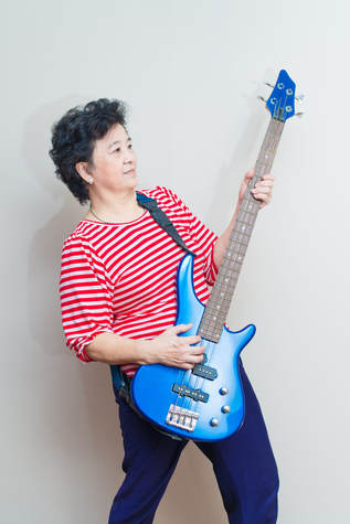 Adult woman playing guitar posing like a rock star, after her guitar lesson.