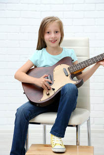 Providence Guitar Academy student holding her guitar and smiling at the camera.