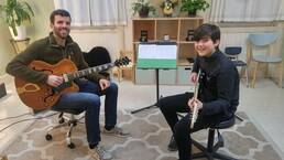 Guitar teacher and student holding their guitars during a lesson.